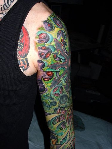 Green Ink Biomechanical Tattoo On Man Left Sleeve