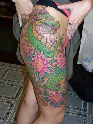 Colored Flowers and Green Dragon Tattoo On Girl Right Thigh