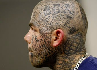 Grey Ink Spider Web And Lettering Face Tattoo